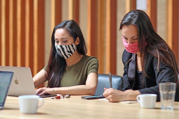 Women working while wearing masks