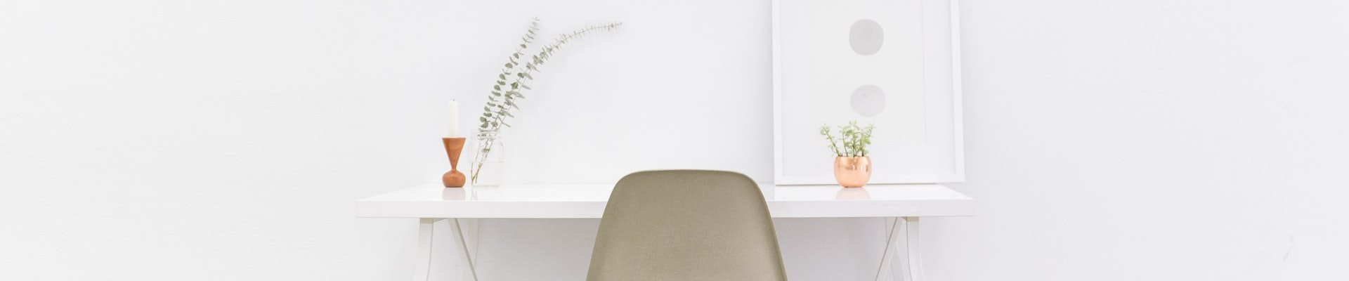 A white chair and desk in front of a wall