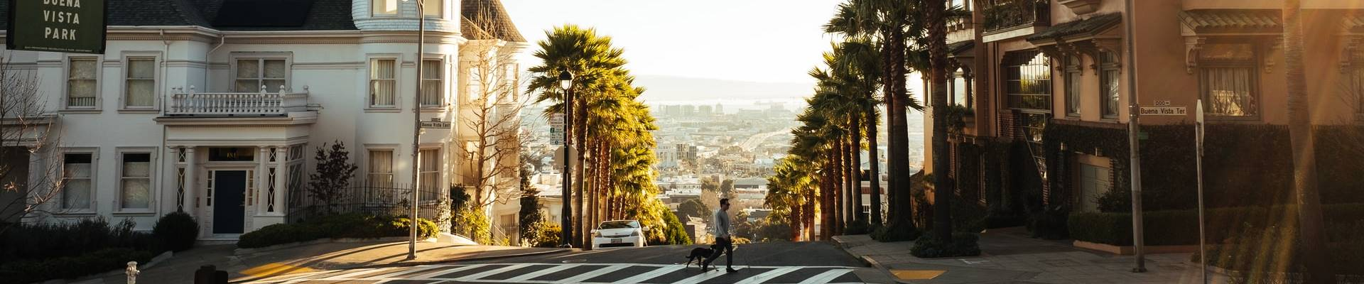 A man walking his dog and crossing the street in SF